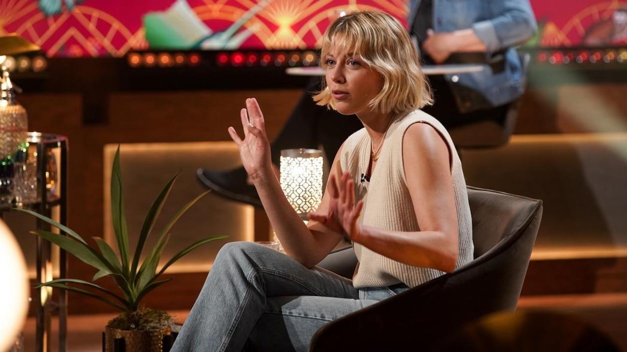 Une femme aux cheveux blonds qui parle en agitant les mains.