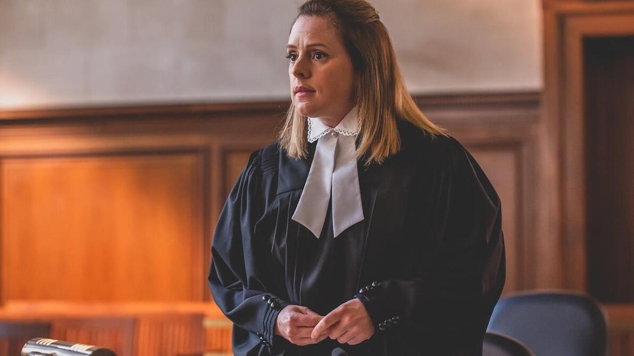 La femme est vêtue d'une toge d'avocate.