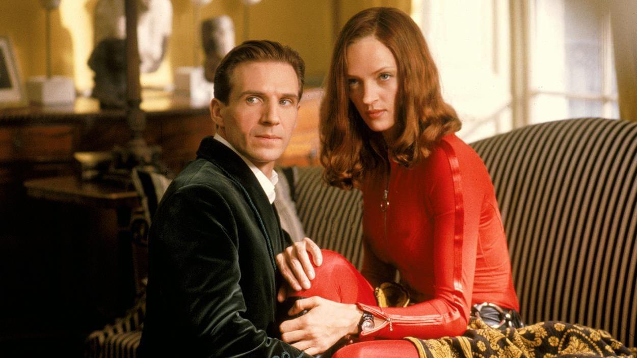 Une femme en combinaison rouge sur un canapé, un homme agenouillé devant elle.