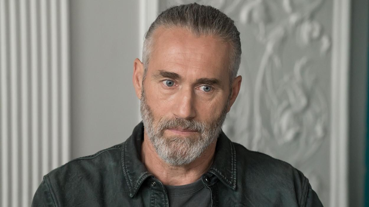 L'homme a l'air songeur. Il porte une barbe, qui est grise, est ses cheveux sont tirés vers l'arrière. Ses yeux sont bleus.