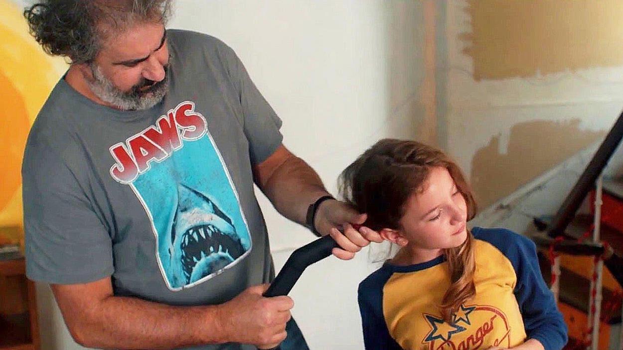 Un homme fait des couettes à une petite fille avec un aspirateur.