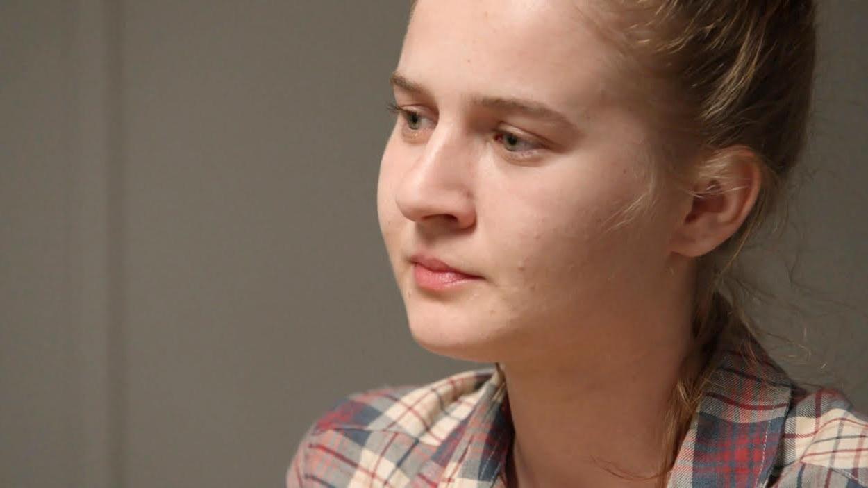 Une jeune femme qui porte une chemise à carreaux.