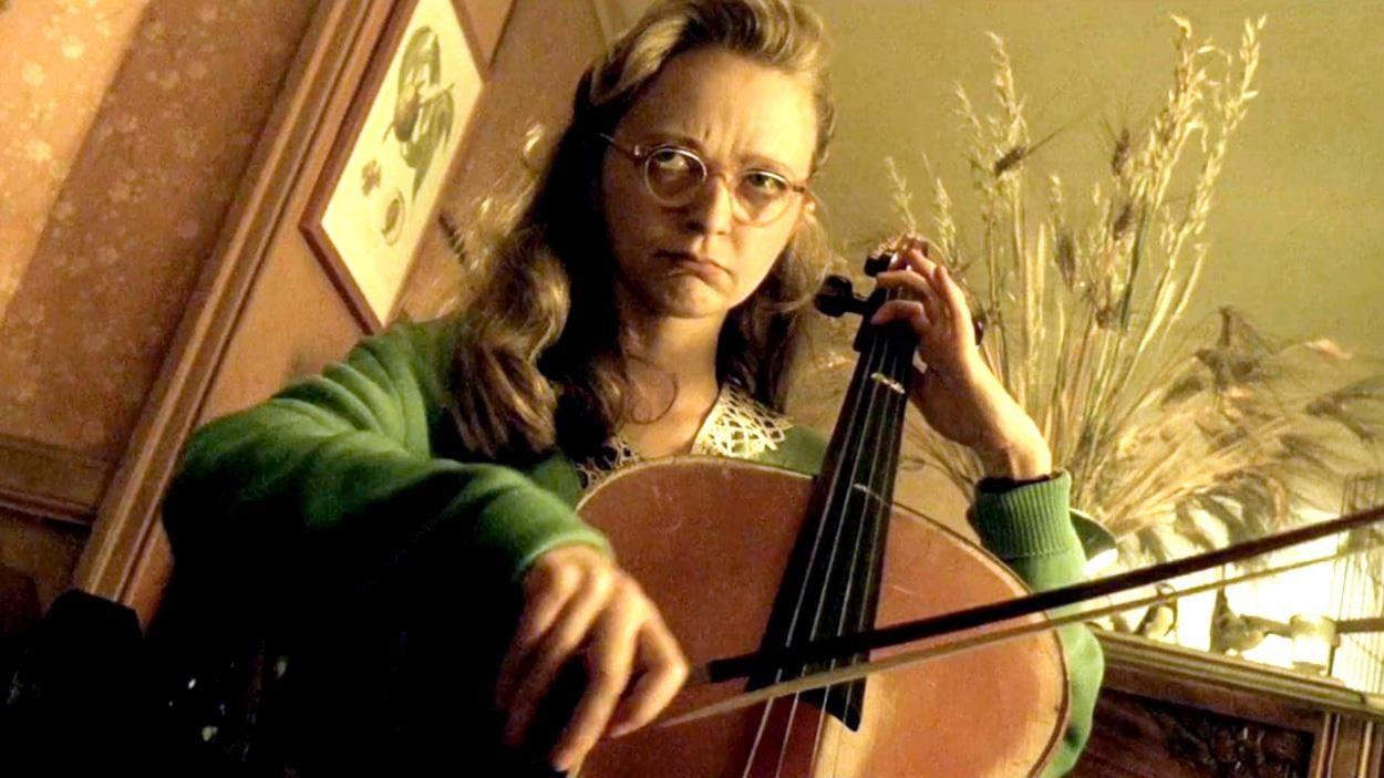 Une jeune femme à lunettes joue du violoncelle.