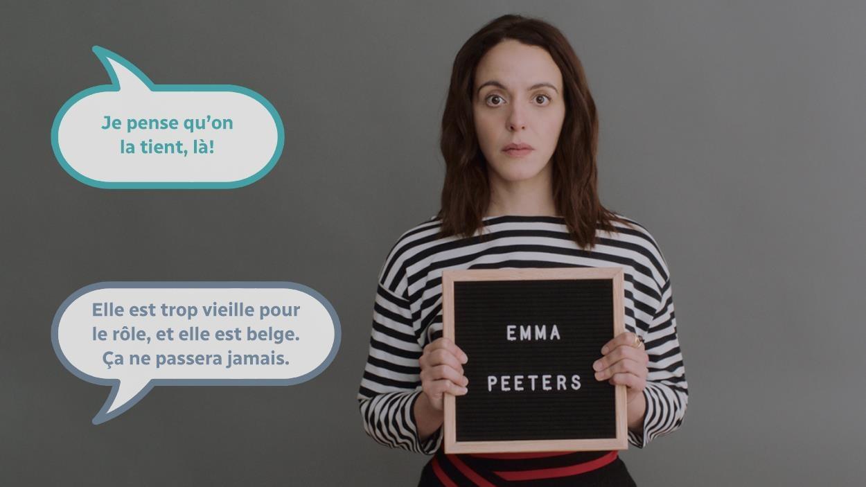 Une jeune femme (Monia Chokri) portant une affichette avec le nom Emma Peeters écrit dessus.