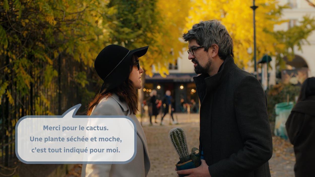 Une femme (Monia Chorki) portant un chapeau et des lunettes noires parle à un homme tenant un cactus.