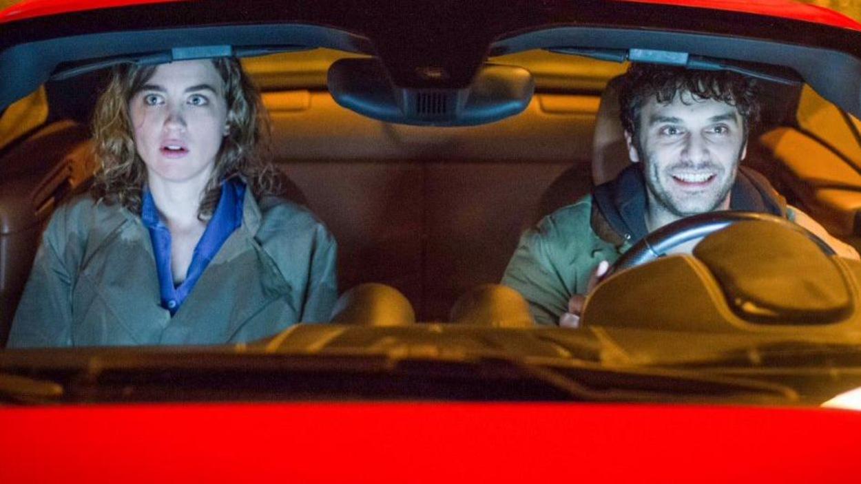 Un homme et une femme dans les sièges conducteur et passager d'une voiture rouge.