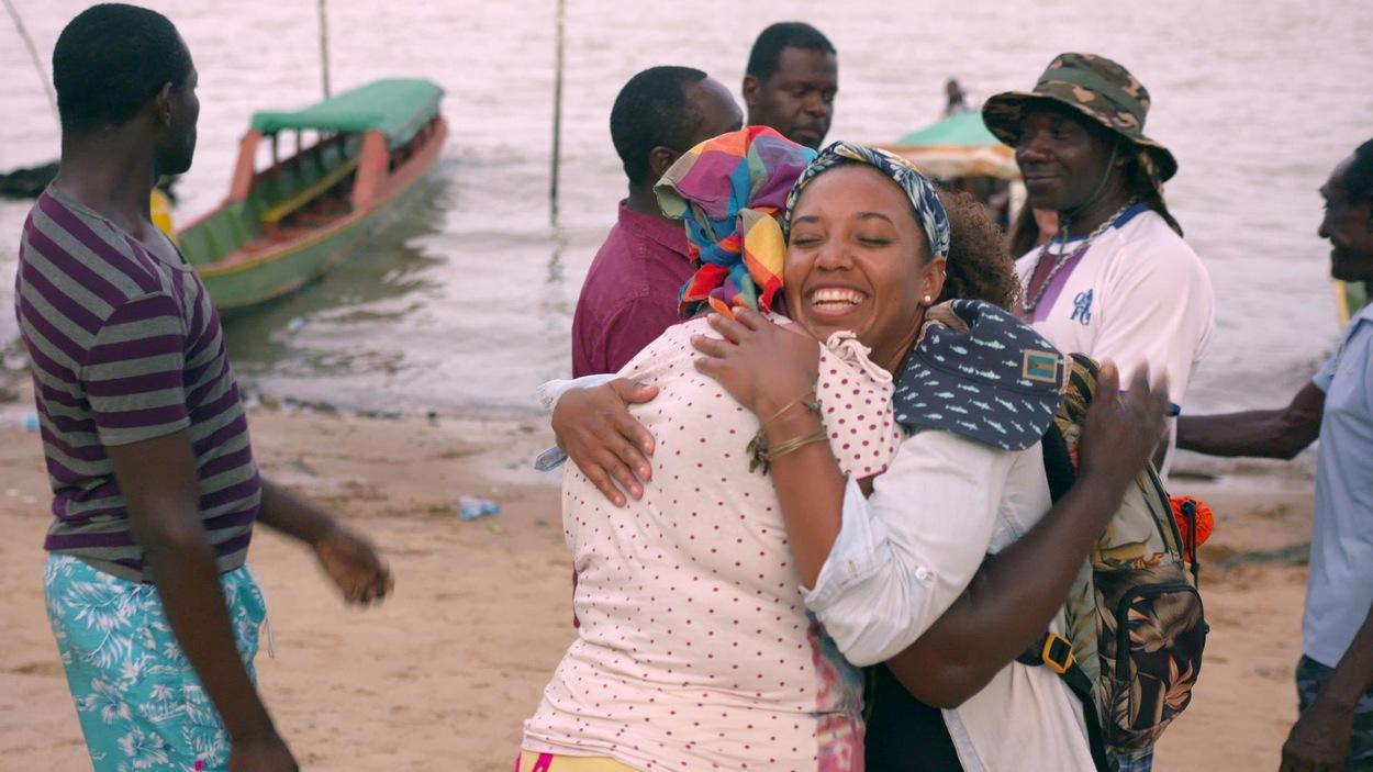 Sur une plage, une femme en enlasse une autre, en souriant.
