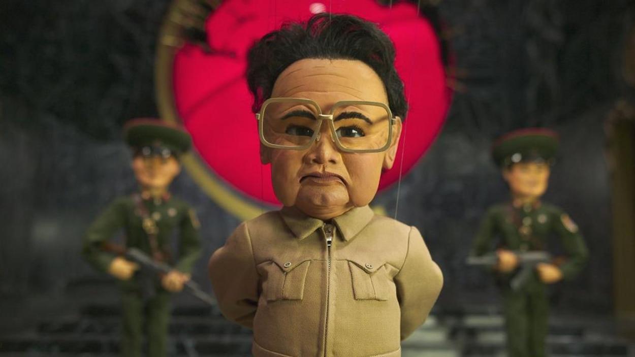 Une marionnette représentant un dictateur en costume sable et avec de grosses lunettes