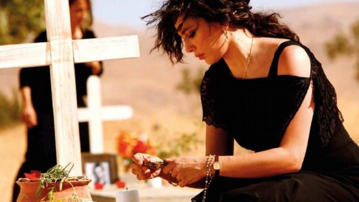 Une femme en noir agenouillée devant une tombe.