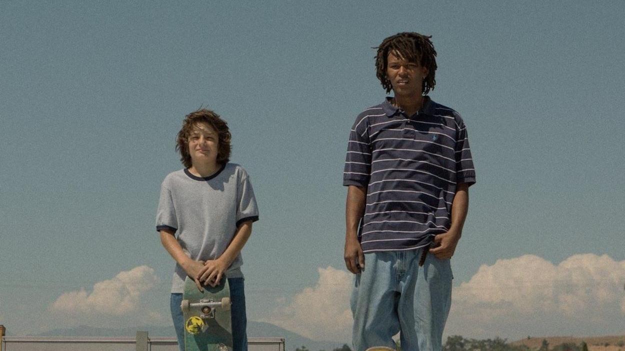 Un garçon et un jeune homme, leurs skates devant eux, regardent droit devant eux.