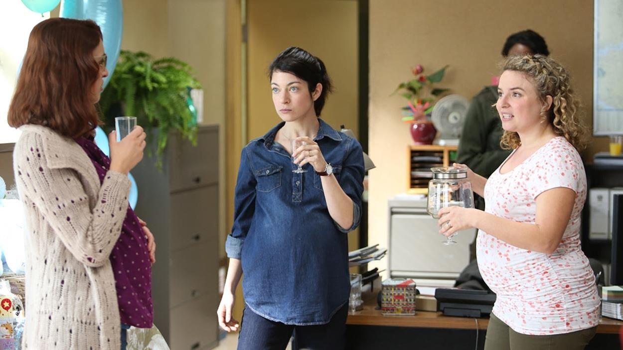 Trois femmes enceintes se parlent, un verre à la main.