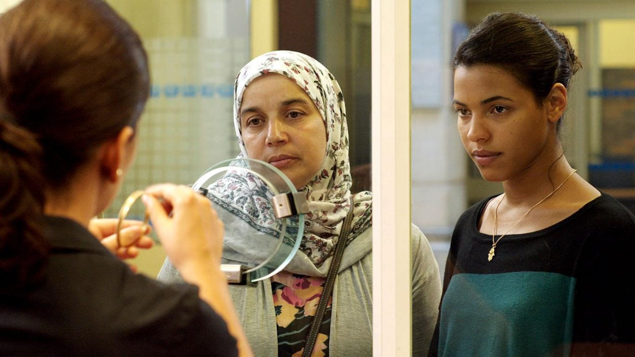 Une femme voilée et une jeune femme derrière un hygiaphone.