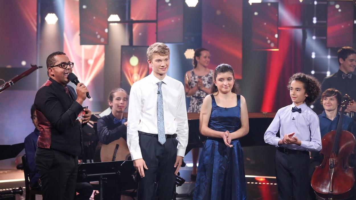 Gregory est sur scène avec Victor, Nikki et Benjamin. Ils sont habillés de façon élégante et sont entourés d'anciens candidats.
