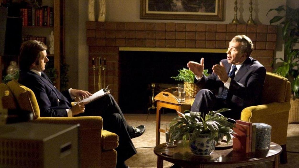 Dans un salon confortable, un homme répond aux questions d'un autre