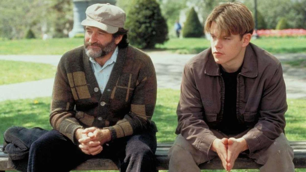 Un homme portant une casquette et une barbe et un jeune homme assis sur un banc dans un parc.