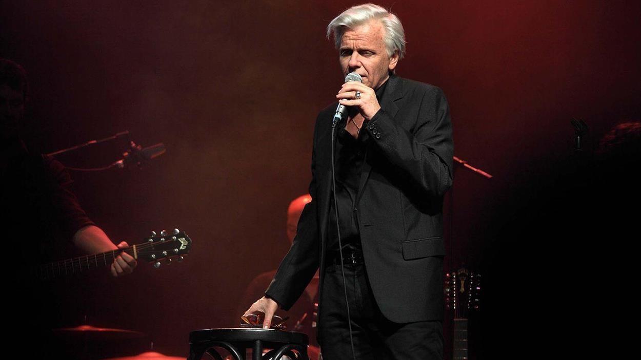 Un homme  à la chevelure blanche, en costume sombre, sur scène en train de chanter.
