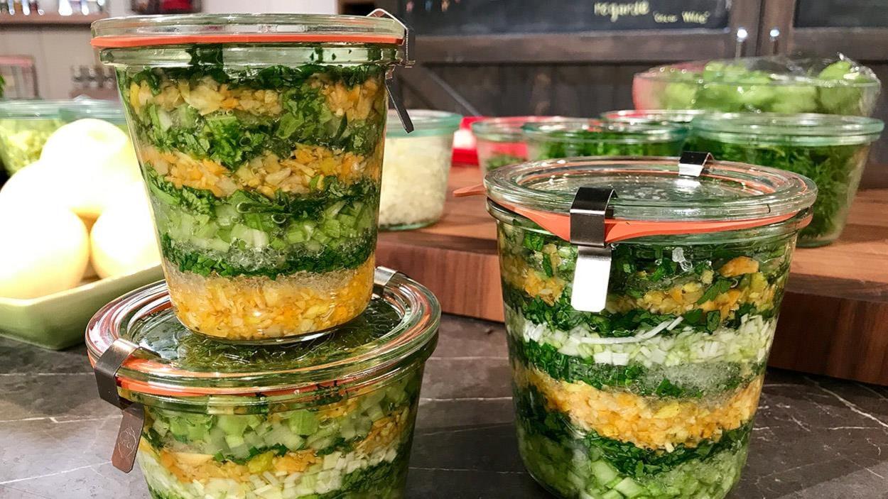 Des pots en verre remplis de morceaux finement hachés de carottes, de poireaux, de céleri et d'oignon