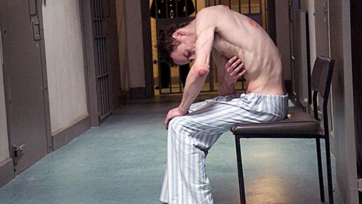Un homme décharné, le torse nu, en pantalon rayé, assis sur une chaise dans un couloir de prison