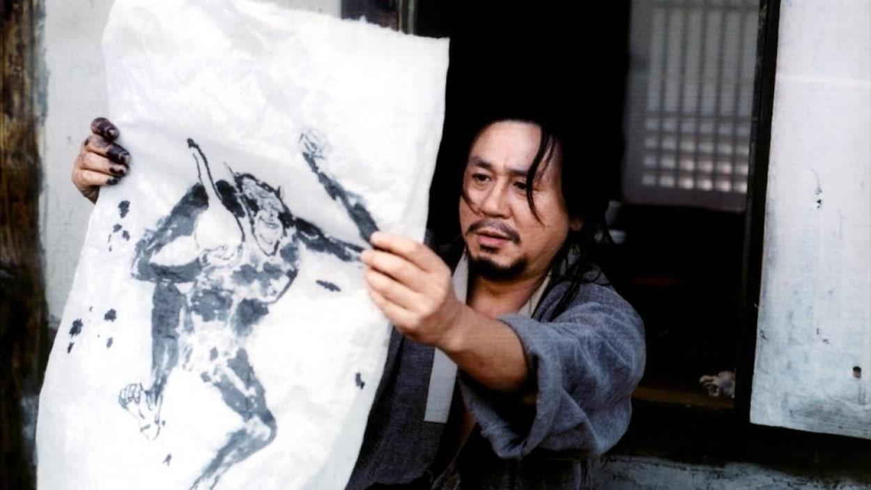 Un homme observe le dessin qu'il vient de faire sur une toile blanche