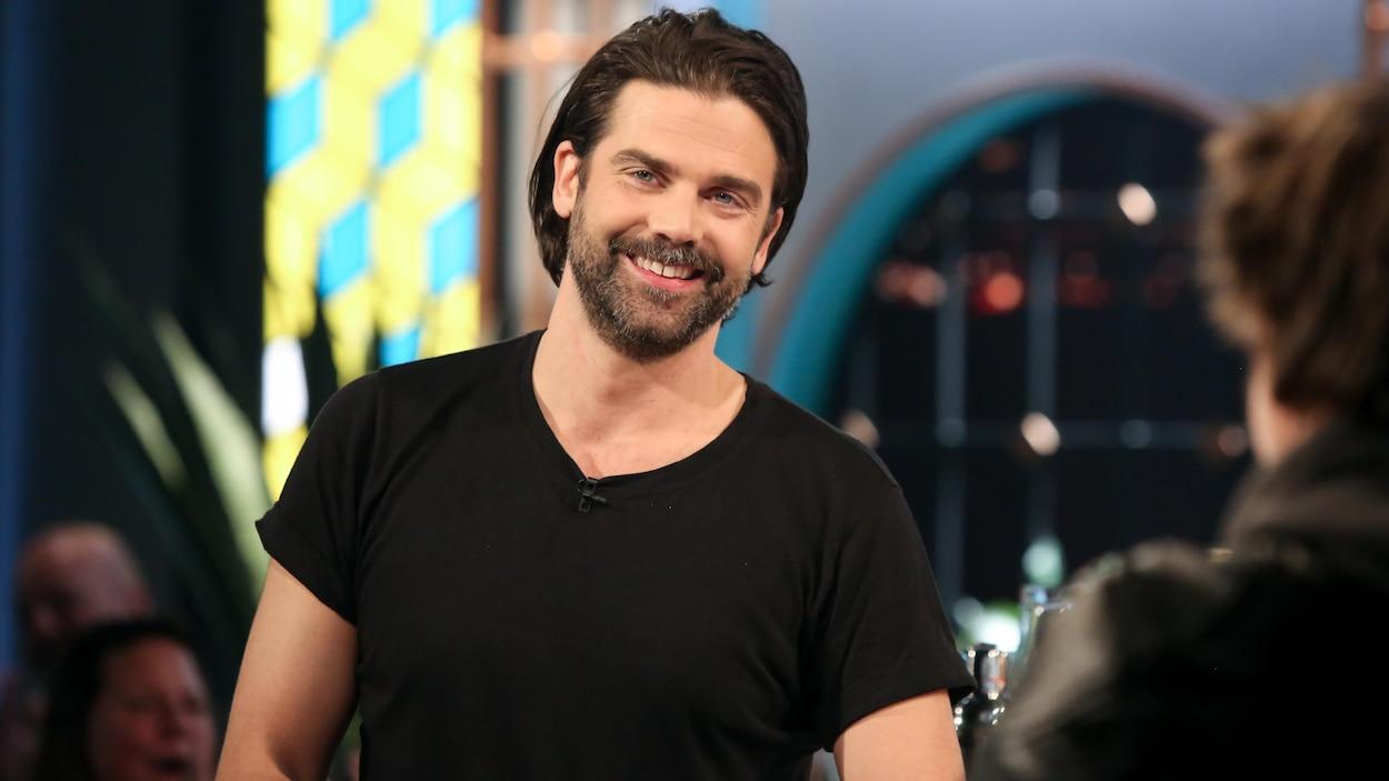Il sourit. Il porte un t-shirt noir.
