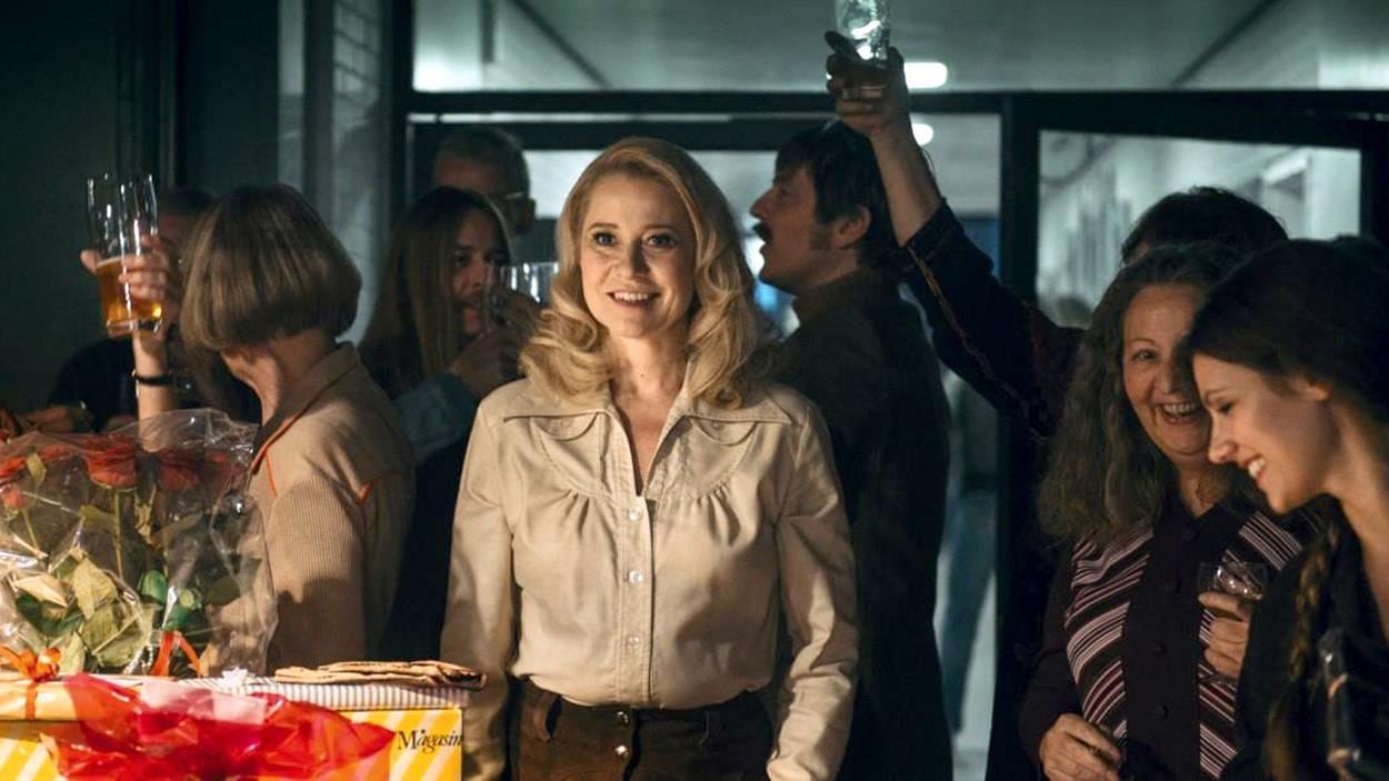 Une femme au milieu d'un groupe de gens riant et levant leurs verres.