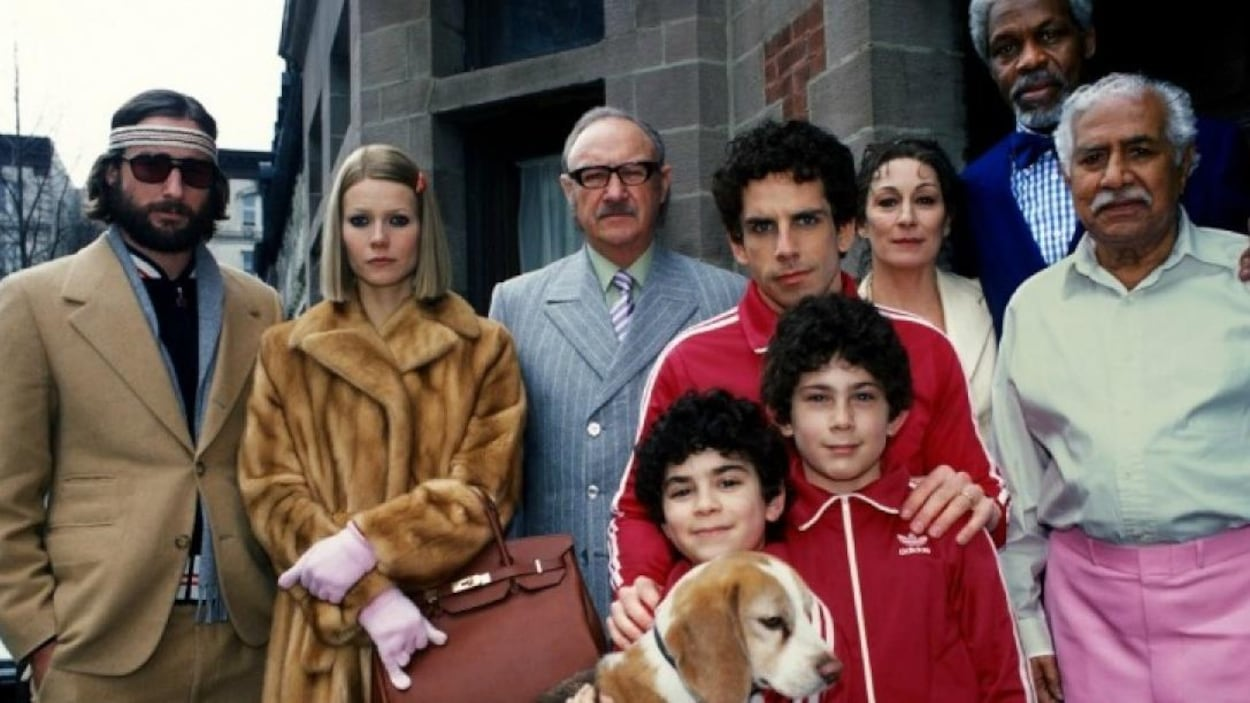 Une famille hétéroclite, avec un homme et ses deux fils en survêtements rouges, une femme en manteau de fourrure et un homme en costume et bandeau de tennis sur le front.