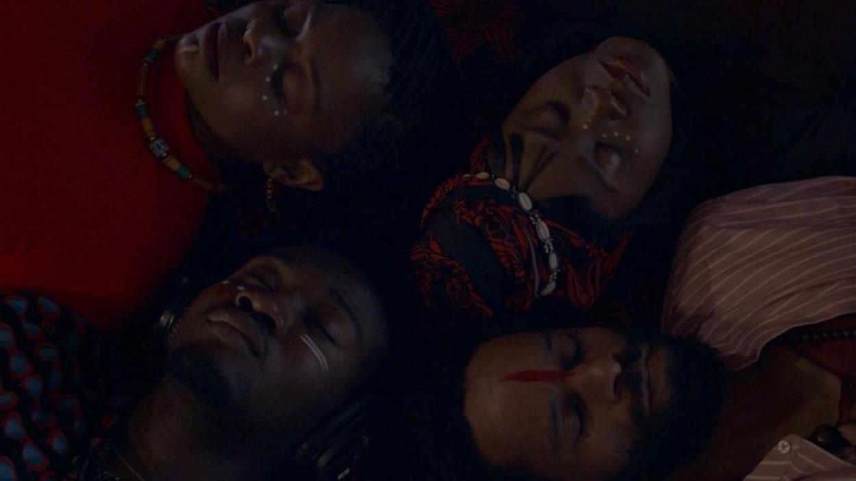 Un groupe de gens, allongés sur le dos, les yeux fermés, les têtes collées.