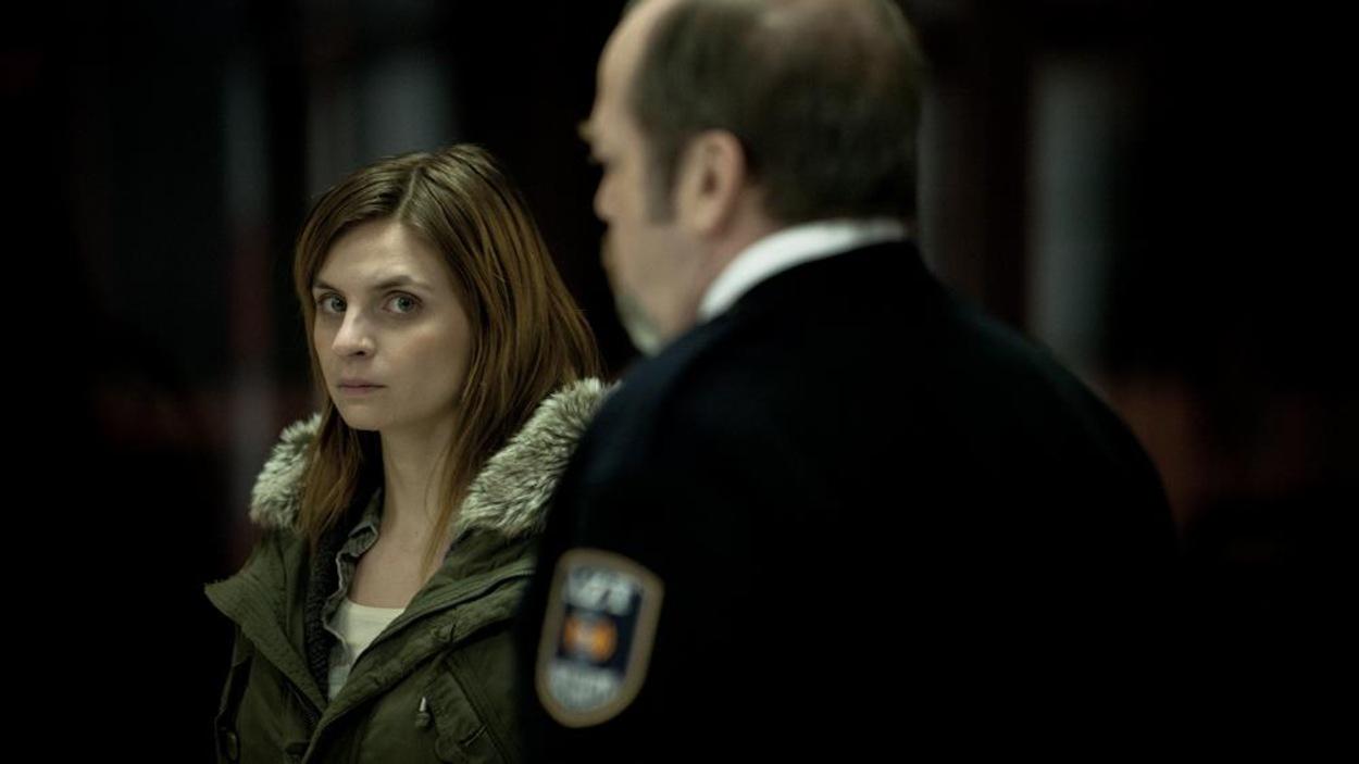 Une jeune femme en veste d'hiver devant un homme de dos, en tenue de gardien de sécurité.