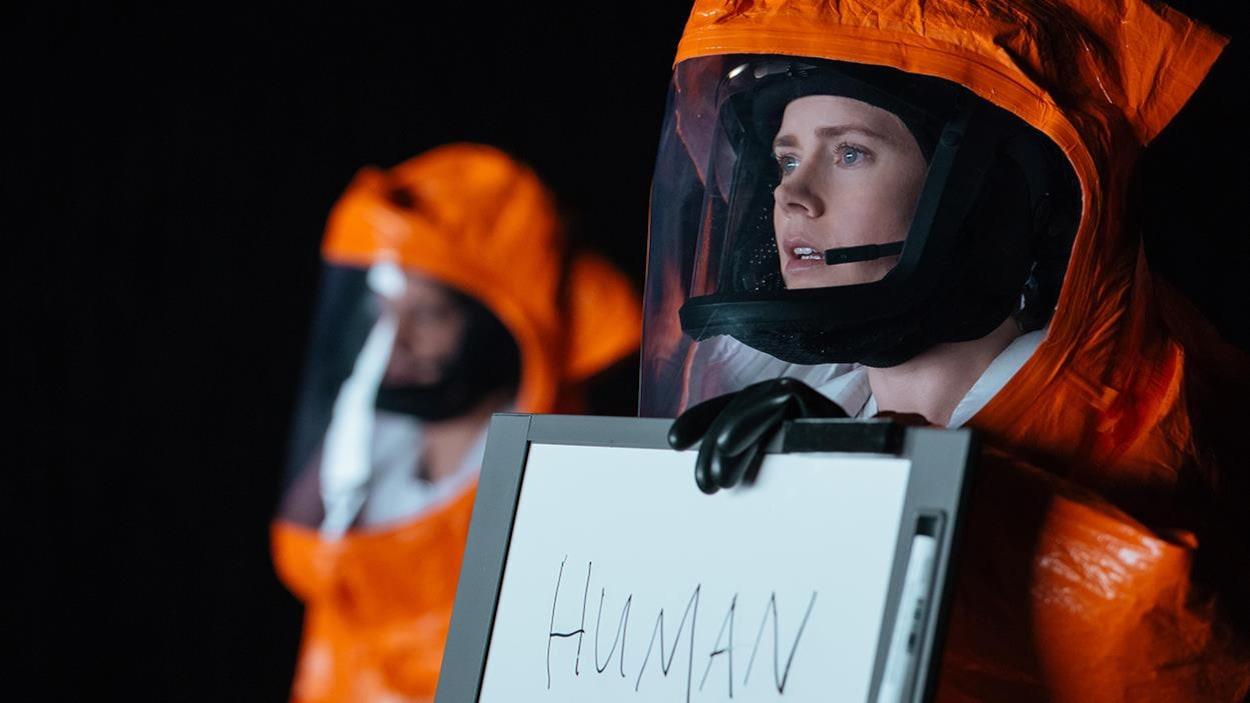 Une femme en combinaison orange tient un écriteau sur lequel est écrit Human.