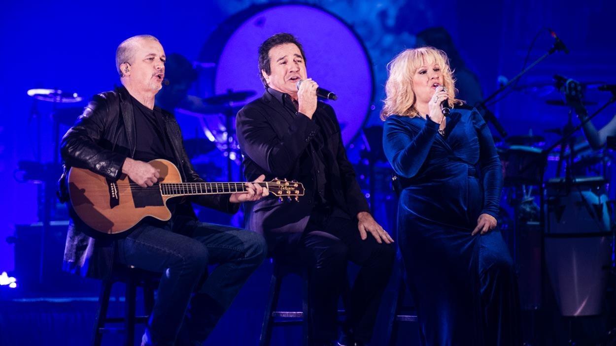 Les trois chanteurs sont assis sur scène, une guitare ou micro à la main.