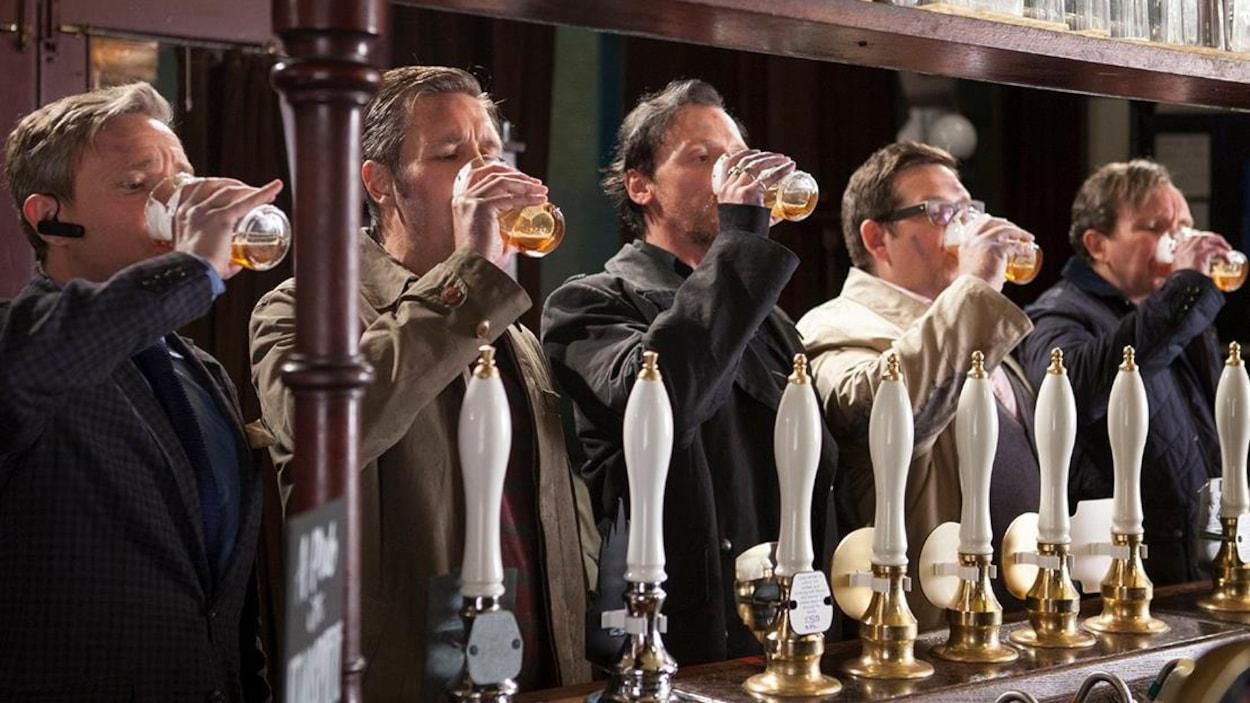 Cinq hommes au comptoir d'un bar boivent une bière.