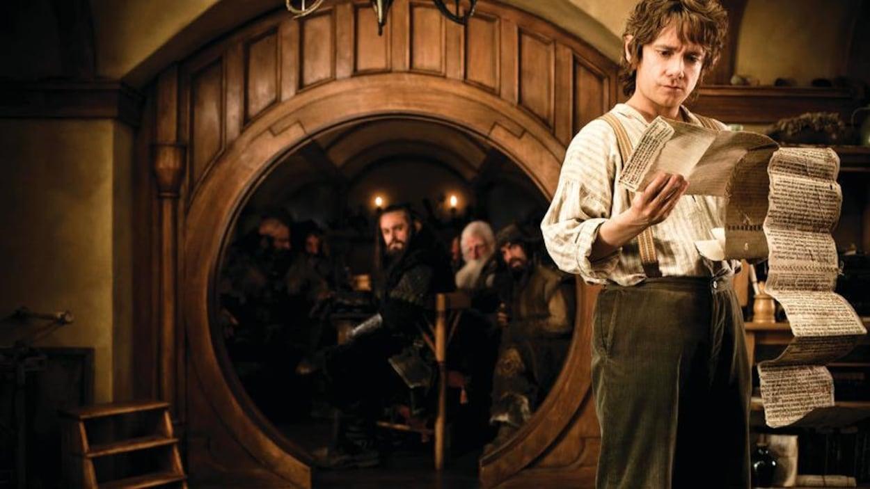 Un hobbit lit une longue lettre devant un cadre de porte rond sous lequel plusieurs hommes sont assis.
