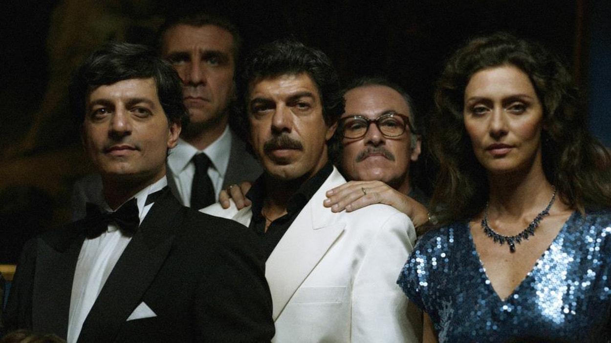 Quatre hommes et une femmes posent ensemble, en tenues de soirée.