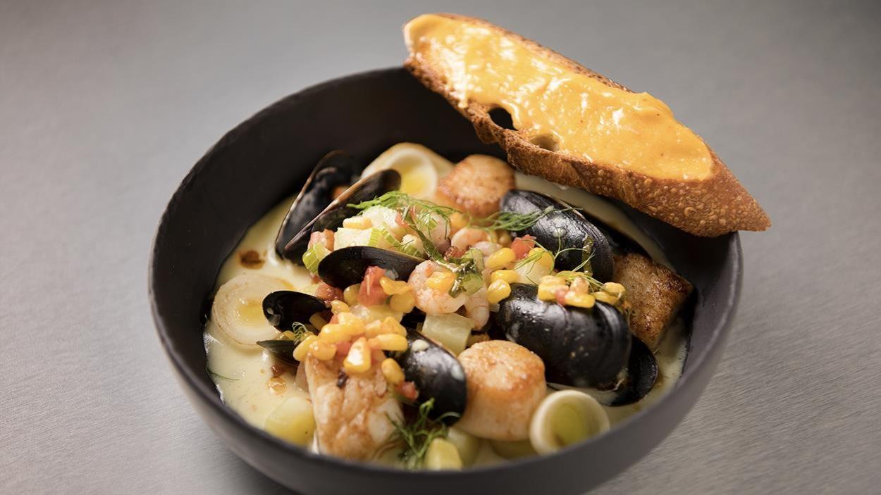 Un bol de chaudrée de fruits de mer et poissons, salsa de maïs et tomate accompagné d'un croûton à l'aïoli.