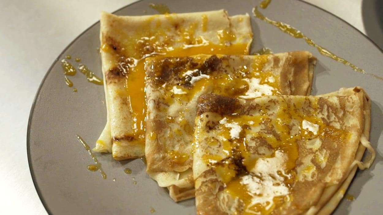 3 crêpes fines aromatisées au miel et à l'argousier dressées sur une assiette.
