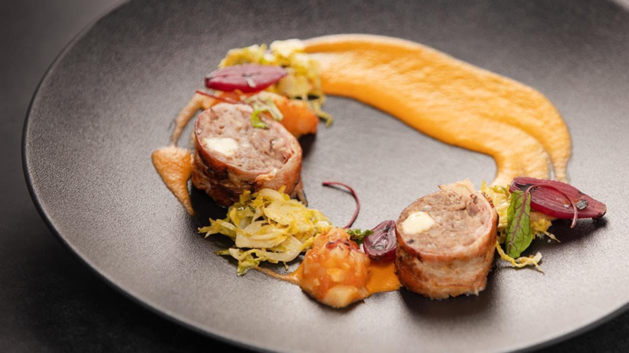 Pain de viande au fromage en grains enrobé de bacon. Coulis de tomates fumées, ketchup aux fruits, embeurrée de choux et oignons marinés.