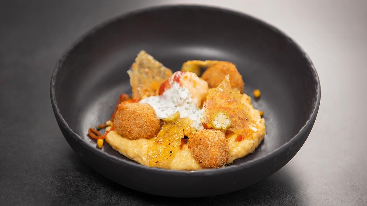 Alligator et homard glacé, garnis d'une tuile de polenta, le tout servi dans un bol rond en terre cuite noire.