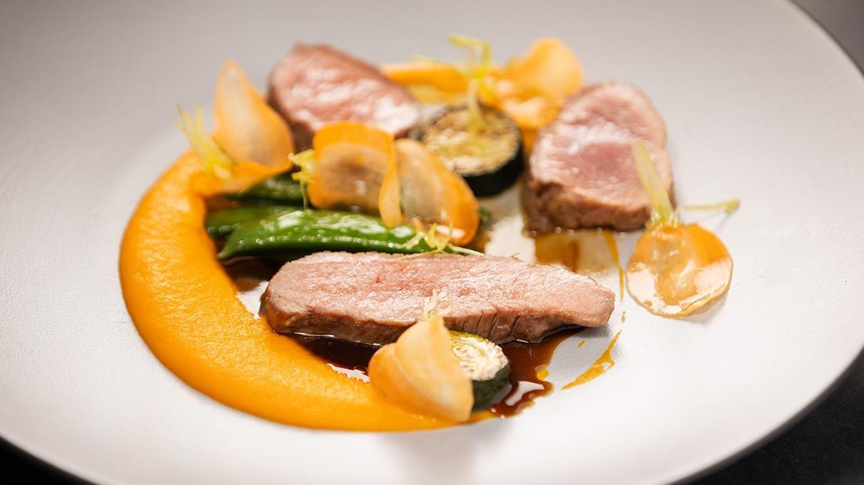 Trois tranches de gigot d'agneau du Québec, purée de carottes, courgettes, pois sucrés, carottes croquantes et sauce au vermouth.