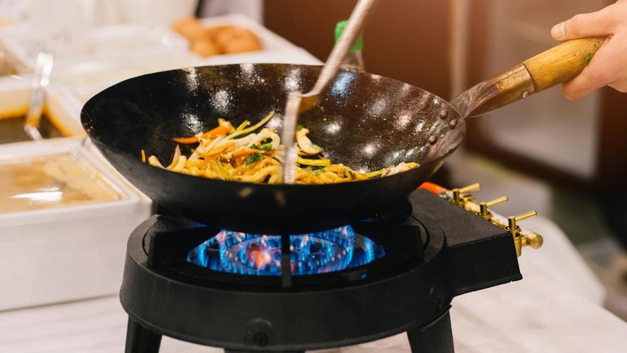 Un chef qui fait sauter des légumes dans un wok.