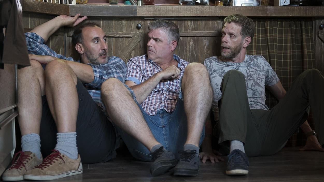 Les trois hommes se cachent, accroupis, près des armoires de cuisine.