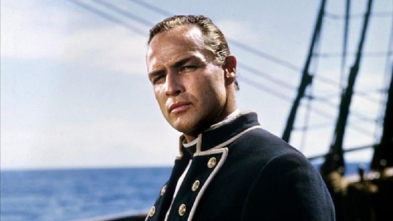Un homme (Marlon Brando) en lieutenant de la marine, sur un bateau.