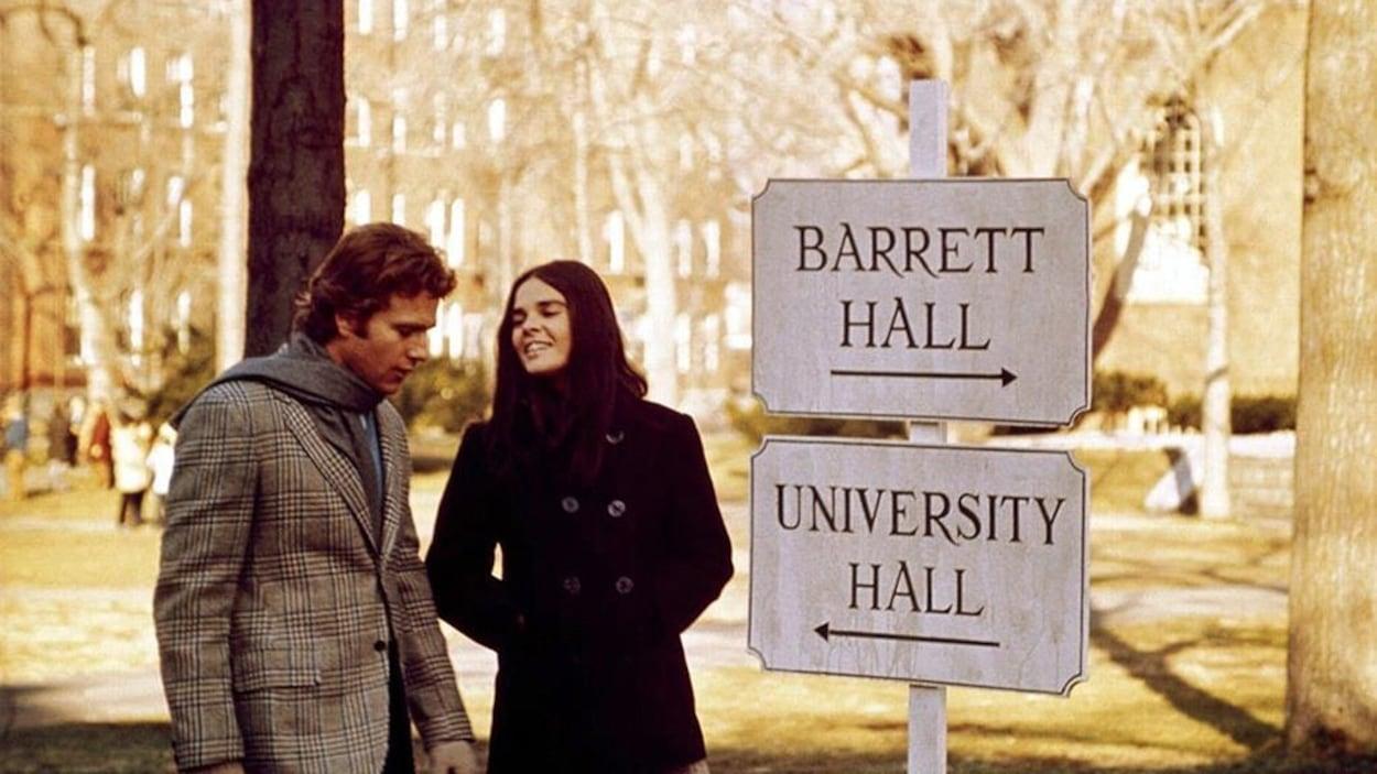Deux jeunes gens se promènent devant des panneaux indiquant des halls d'université.
