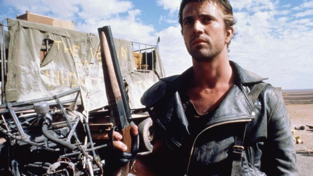 Un homme (Mel Gibson) en blouson de cuir, avec un fusil dans le désert.