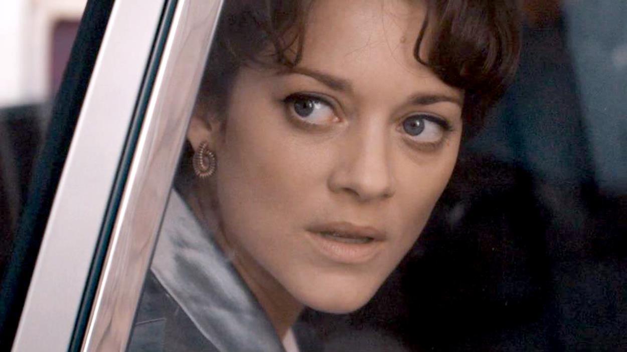Une femme en gros plan, derrière une vitre de voiture.