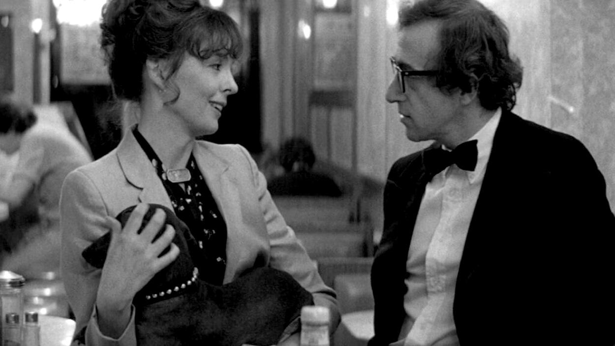 En noir et blanc, une femme parle à un homme qui porte un tuxedo, dans un diner.