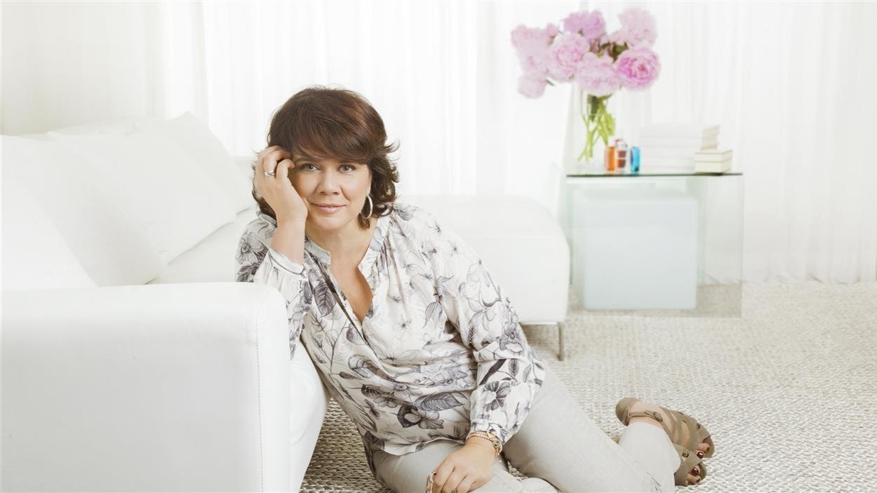 Elle est assise par terre, appuyée sur un canapé blanc