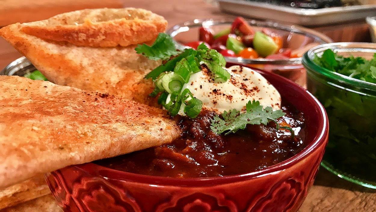 Un bol de chili avec de la crème sure et des oignons verts.