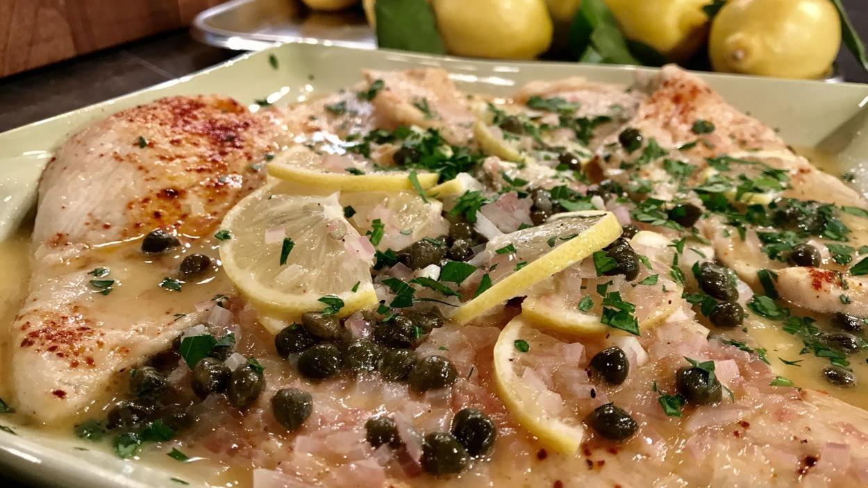 Un plat de poulet garni de câpres et de citron.