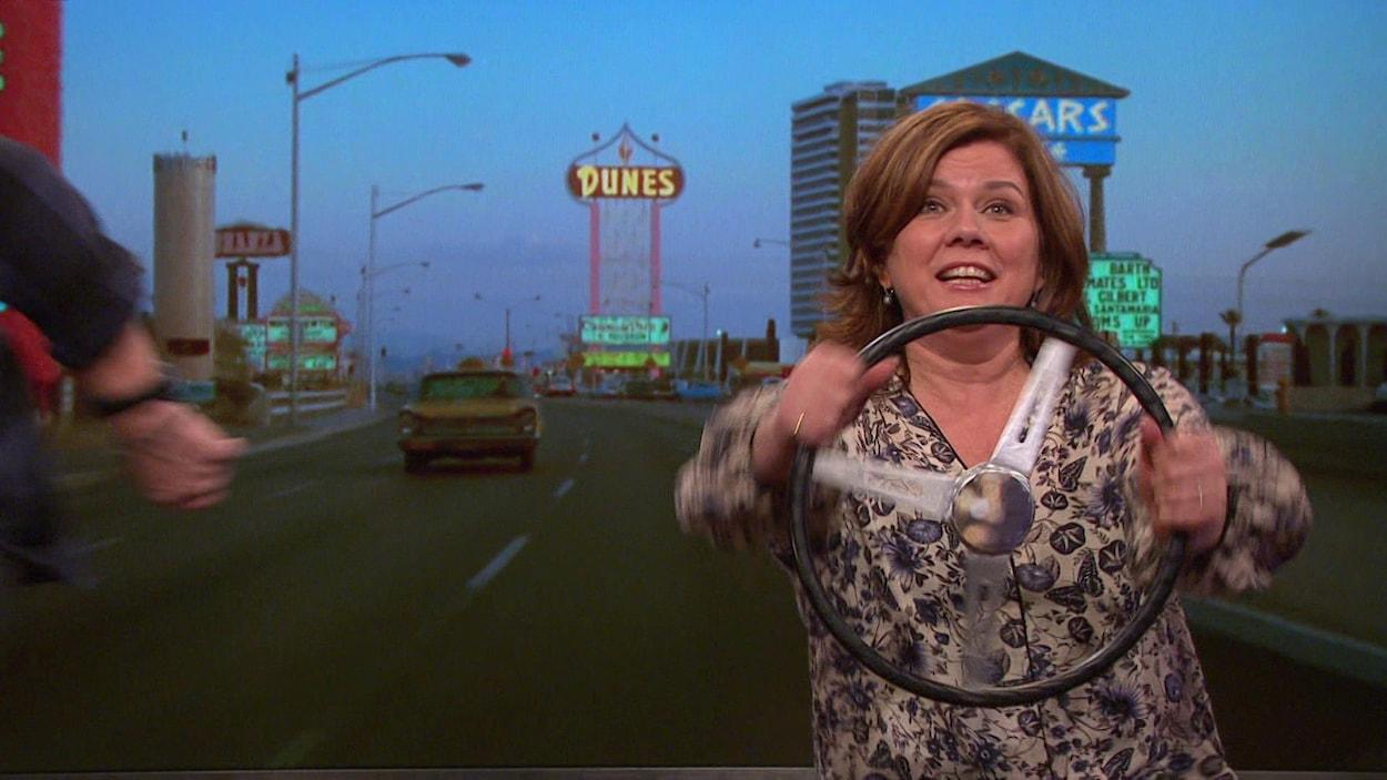 Elle tient un volant et faite mine de conduire dans un faux décor de Las Vegas.