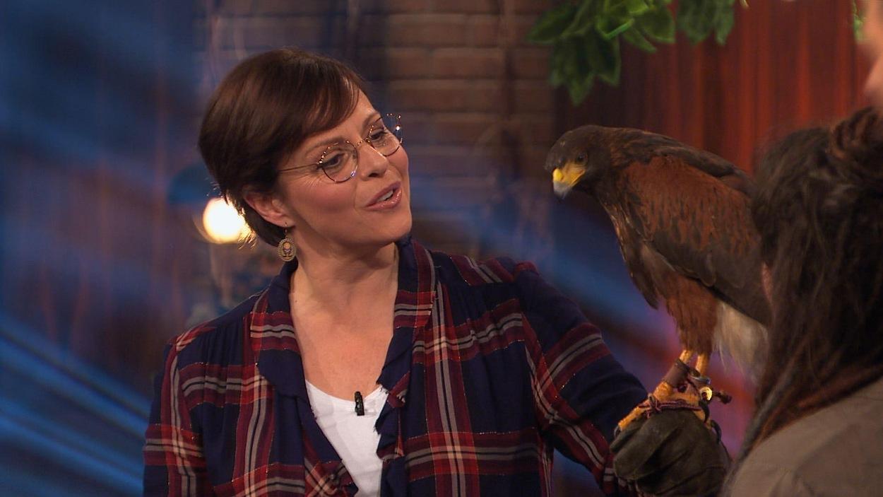 La comédienne a un gros oiseau sur son bras.